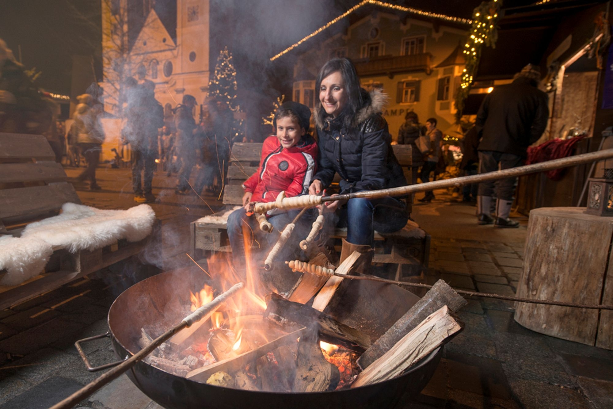 Family cooking food over the fire at St Johann Christmas market