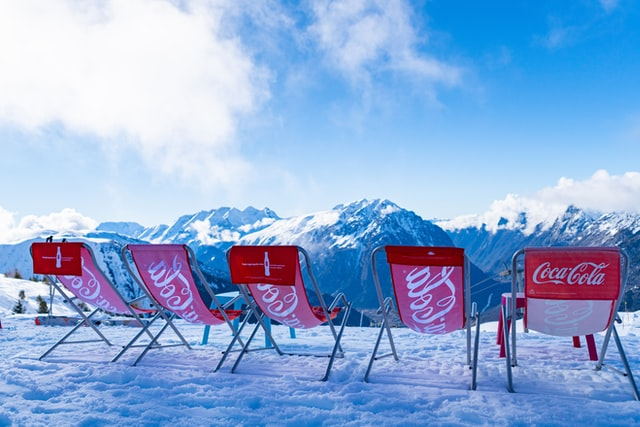 5 deckchairs on top of a snowy mountain