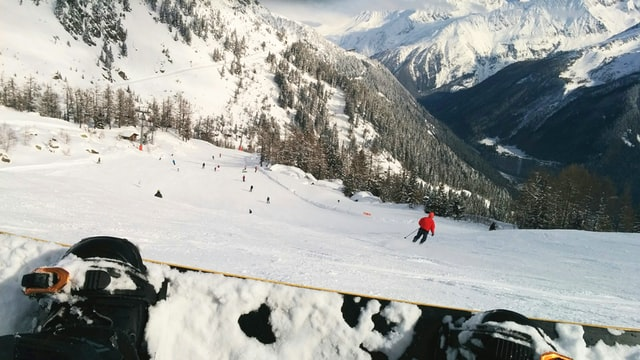 Sitting snowboarder watching a skier in a red jacket skiing down a piste