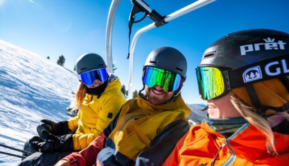 3 skiers sitting on a chairlift laughing at each other