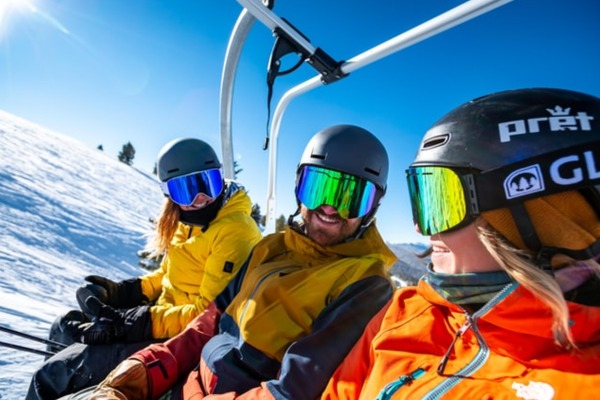 3 skiers sitting on a ski lift talking to each other