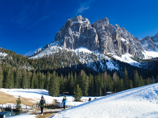 Group of skiers walking with their skis up a mountain in the Dolomites