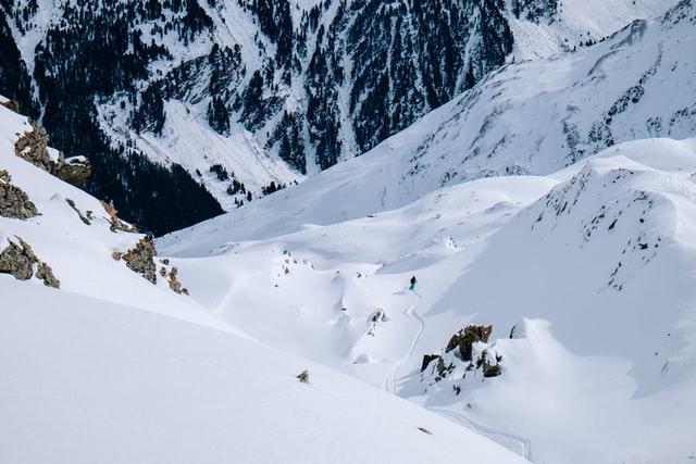 A solo skier skiing off piste through a mountain valley in Austria