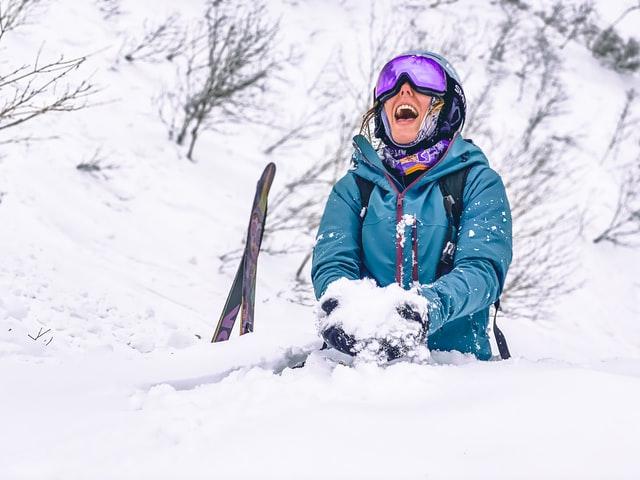 Happy lady dressed in ski wear sitting in the snow in Niseko