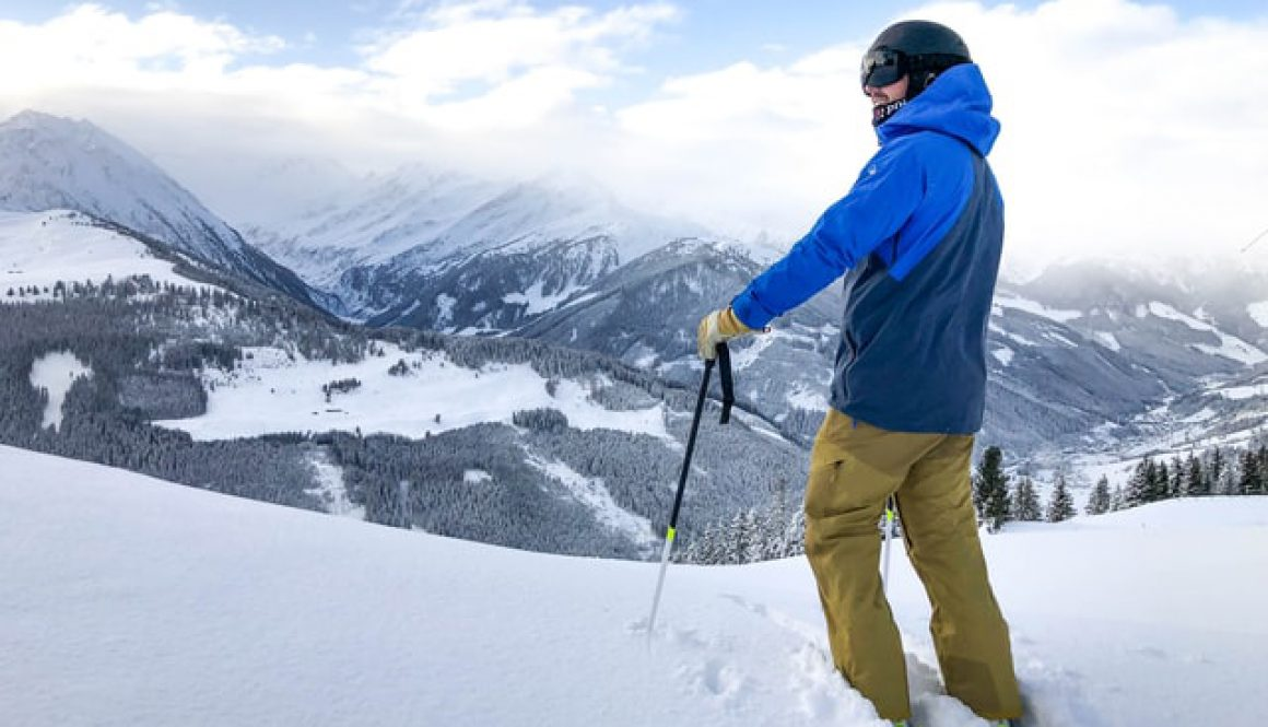 Male skier wearing a blue ski jacket standing at the top of a snowy hill looking down into a forest