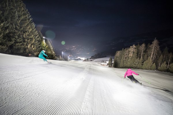 2 skiers skiing down a piste at night in Alpbach