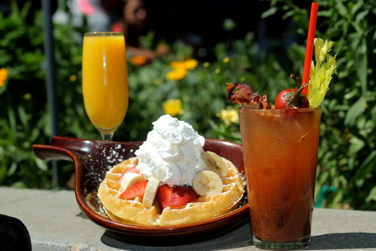 Thick pancake with strawberries and banana, next to a Bloody Mary cocktail and glass of orange juice.