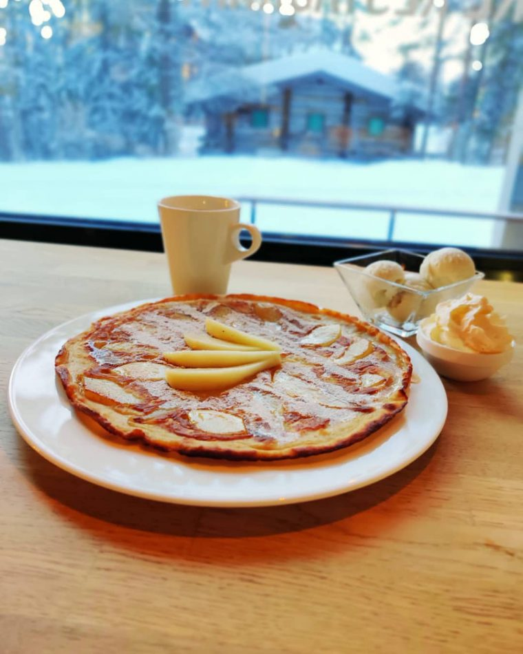 Sweet pancake covered with pears and syrup, next to a window