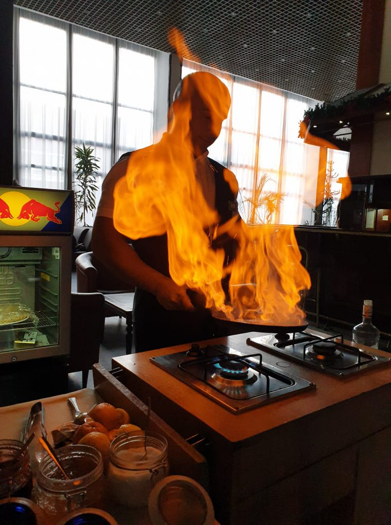 Man frying a pancake with flames coming from the pan