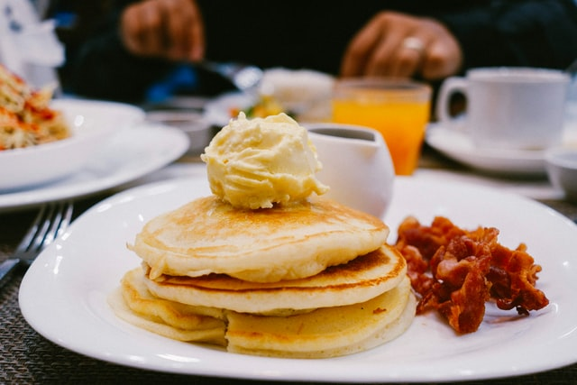 Stack of small & thick pancakes with rashers of bacon on the side