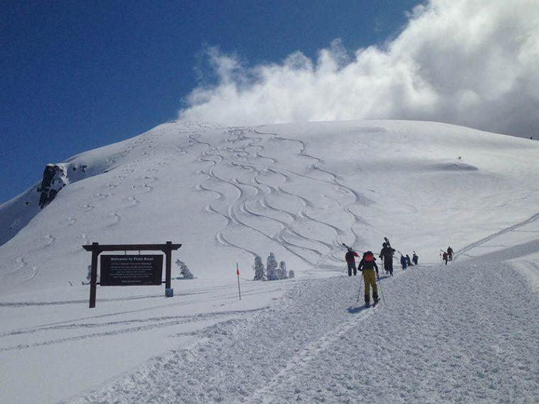Group of skiers walking along a mountain ridge in Whistler