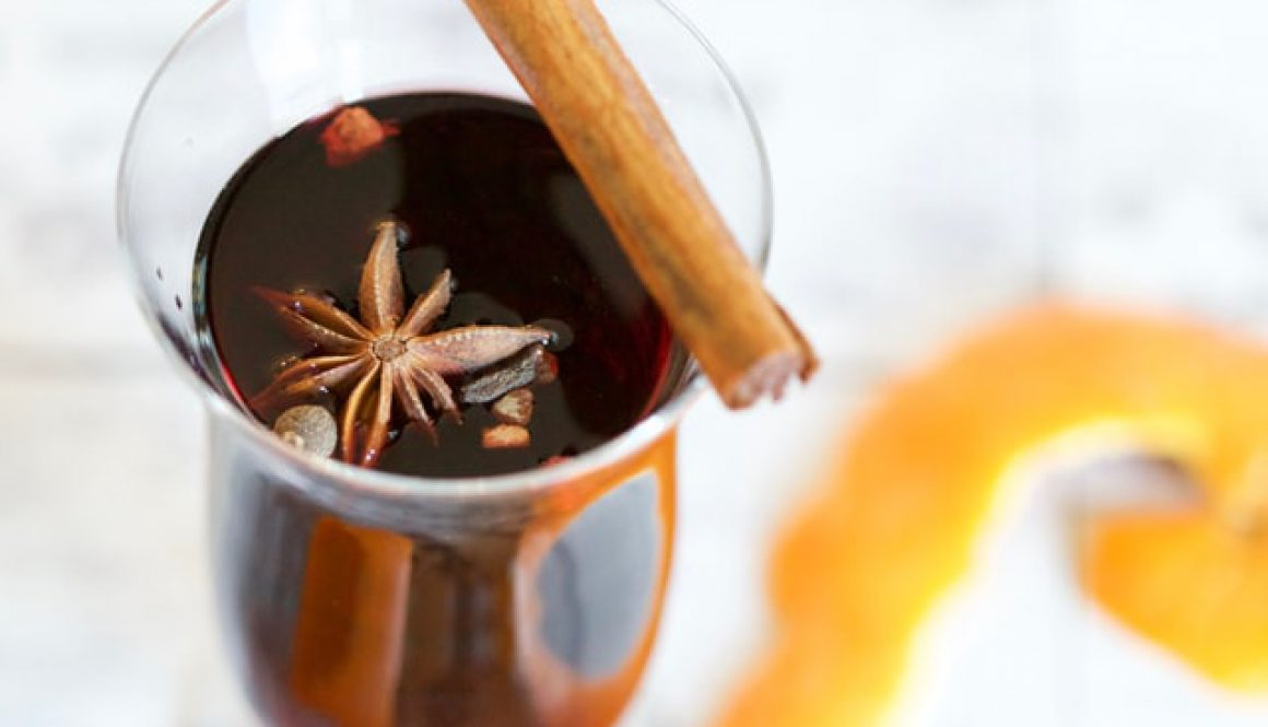 Close up of a glass of mulled wine with a star of cloves sitting at the top of the drink