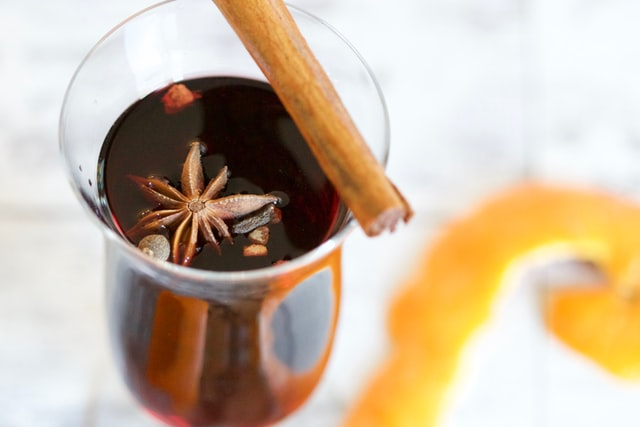 A small glass of mulled wine garnished with star anise and a cinnamon stick