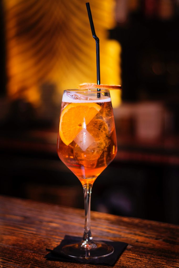An aperol cocktail on the side of a bar