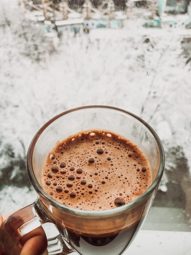 A hand holding a clear mug of hot chocolate against a snowy background