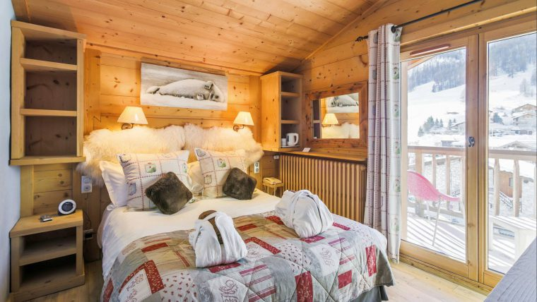 A large cosy bed with in a wooden room with large windows showing a view of the mountains