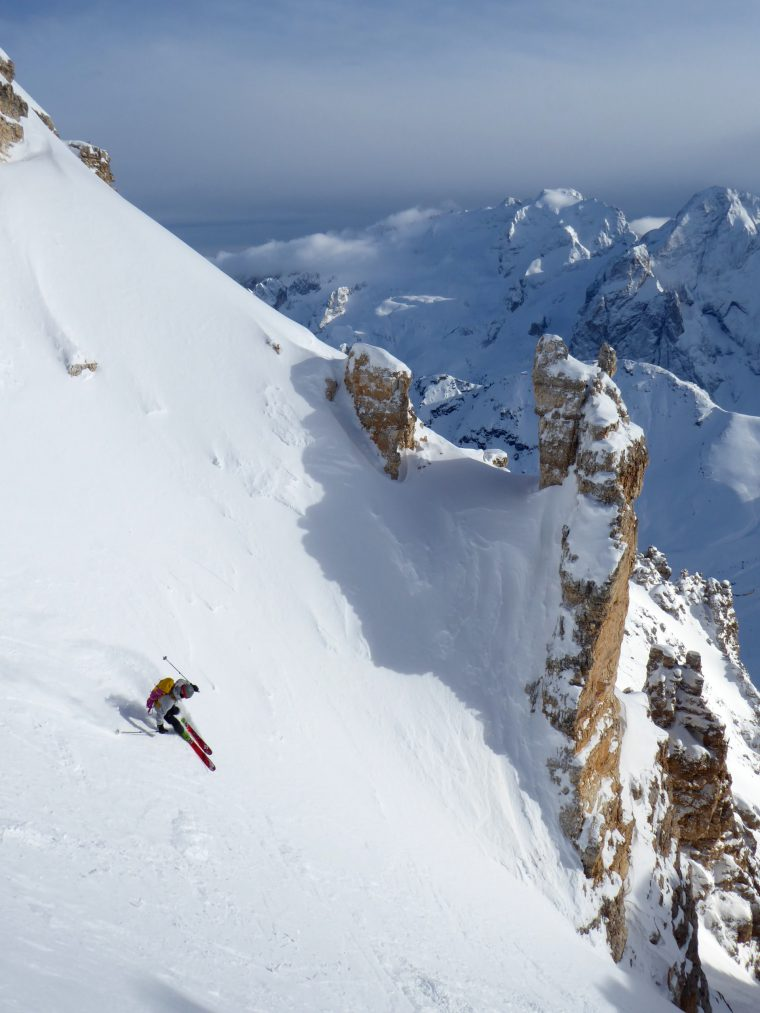 Skier with backpack skiing down steep mountain face
